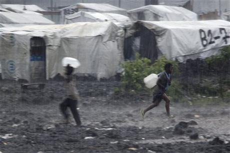 3. Correndo in cerca di un riparo dalla pioggia battente, due bambini trasportano taniche d'acqua in un campo profughi a ovest di Goma, il Mugunga 3. Lunedì 26 novembre 2012. Sono campi come questo, quelli in cui avvengono alcuni dei reclutamenti forzati denunciati da Human Rights Watch (Fonte: AP Photo/Jerome Delay).