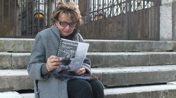 L'autrice Maddalena Lunardello Lenti, fotografata nel 2013 sulla scalinata della chiesa di San Francesco a Schio, tiene in mano una bozza del suo libro. (Fonte: www.ilgiornaledivicenza.it)